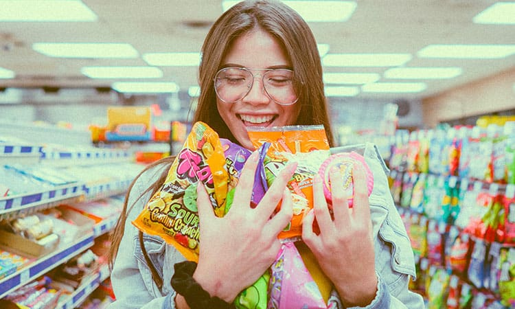 a girl holding packs of sweets in a store