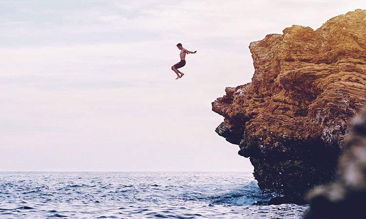 a man jumping off a cliff inside water