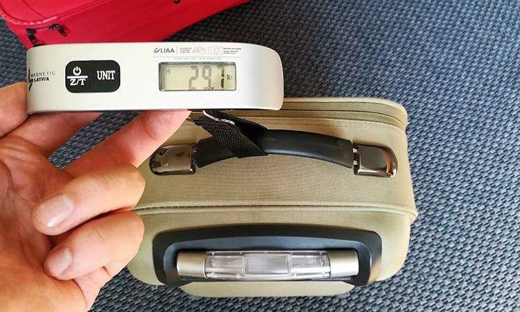 measuring the weight of a suitcase with a luggage scale