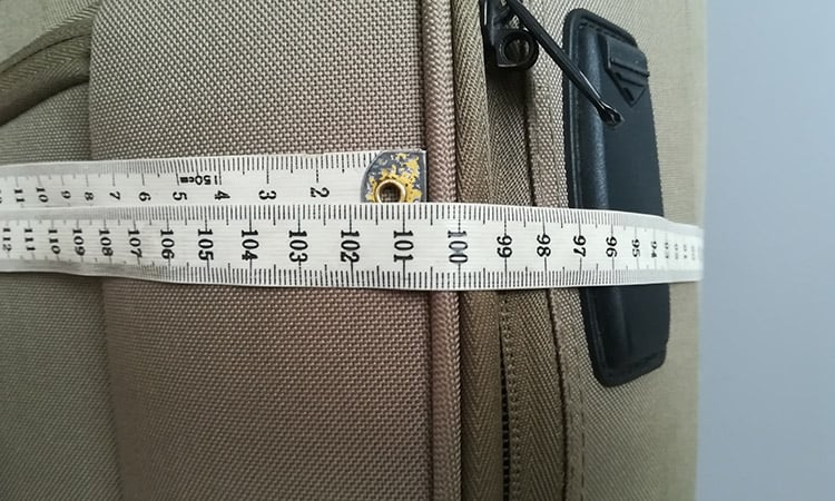 measuring luggage with a measure tape