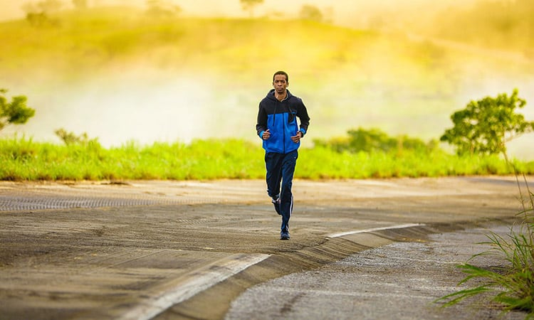 a man with earphones running in the morning