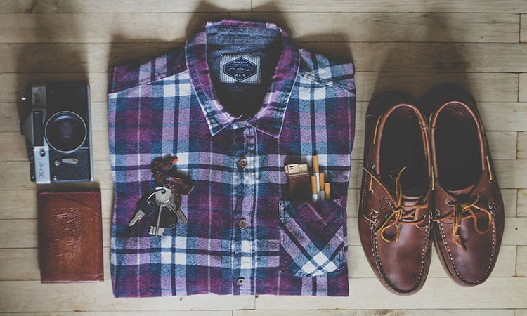 top view of a shirt, shoes, wallet, and a camera