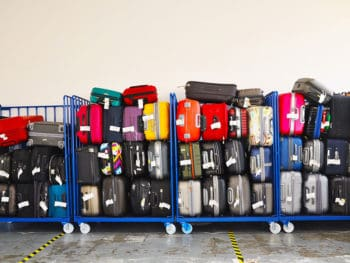 various luggage brands stacked in luggage carts