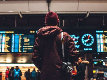 a man with a camera standing in an airport