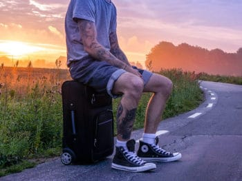 a man on a road sitting on a black carry-on
