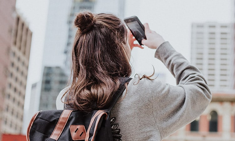 A girl with a backpack taking a photo with mobile phone