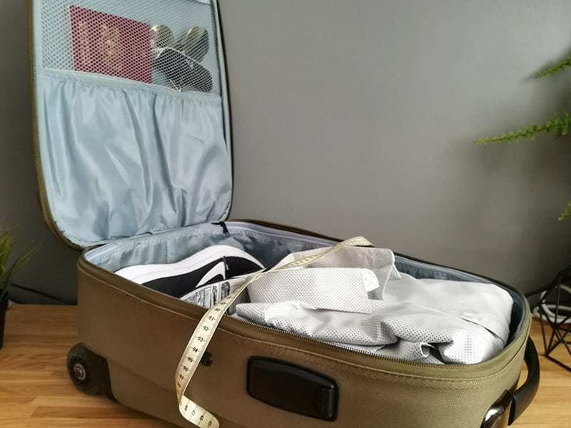 Open suitcase packet with clothes and measuring tape