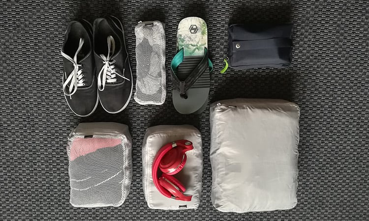 top view of packing cubes laid out next to shoes