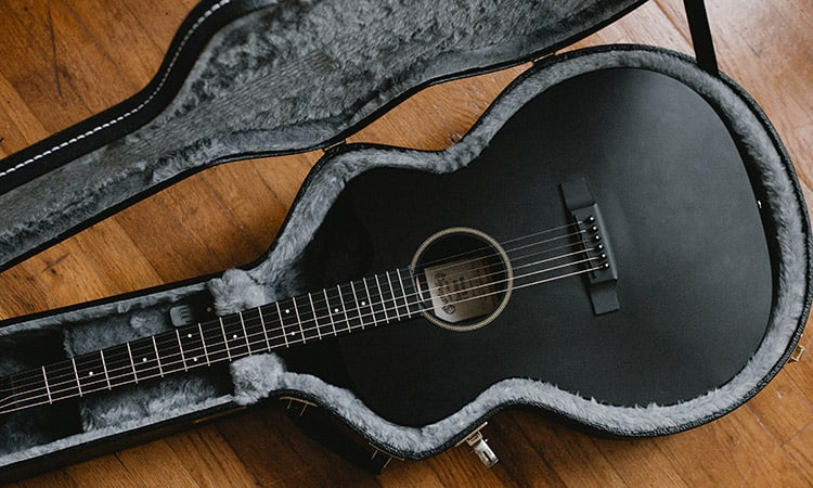 a black guitar inside an opened black leather case