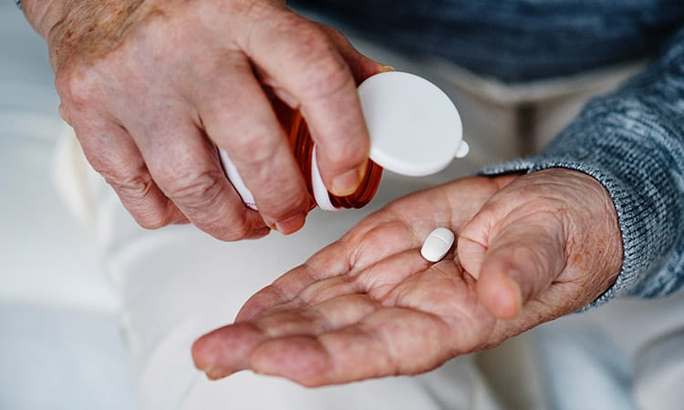 A senior taking out a pill from a bottle