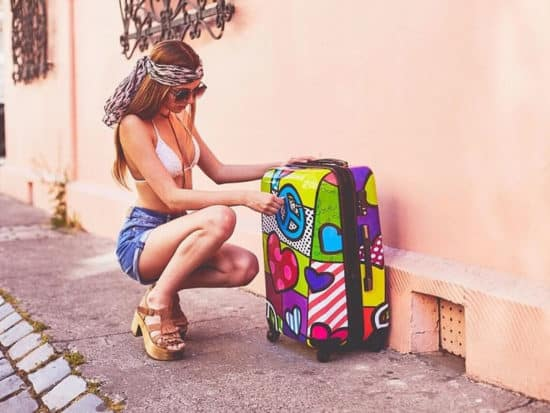 A girl crouching next to the Mia Toro Italy Peace and love carry-on