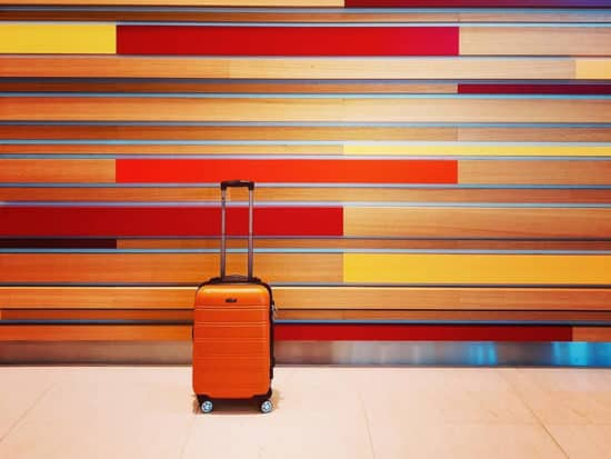 An orange Rockland suitcase on a colorful background