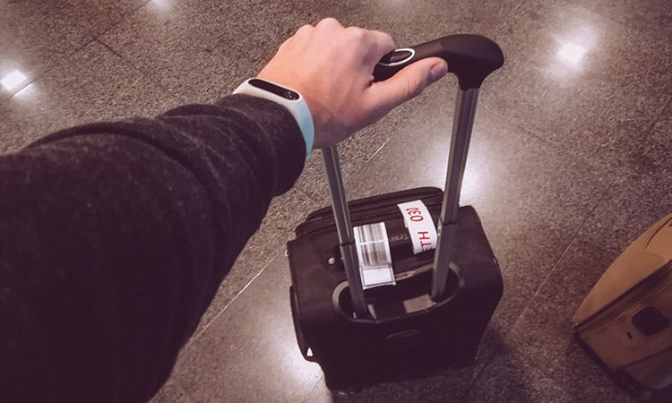 A man holding travelpro maxlite 5 carry-on by the top handle