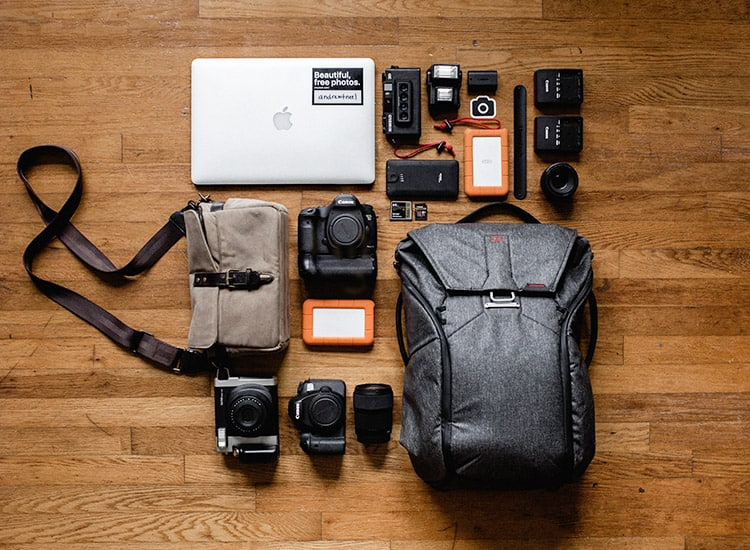 a laptop and other electronics with a laptop backpack laid out on a wooden background in flat lay