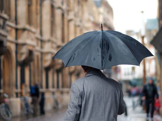 a man with a gray coat in the rain walking with a black umbrella