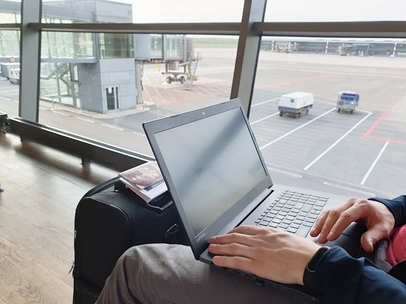a man using a laptop inside an airport
