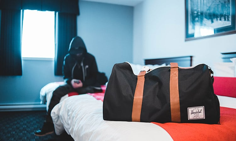 a personal item black duffel on a bed