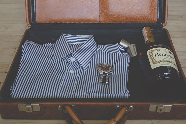 a wine bottle, shirt, and a watch in a leather suitcase
