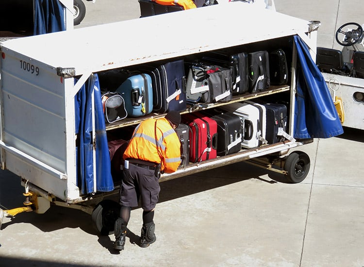 a baggage handler unloading checked luggage from an airport truck