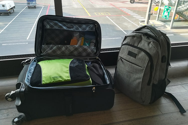 a carry-on and a backpack opened in an airport