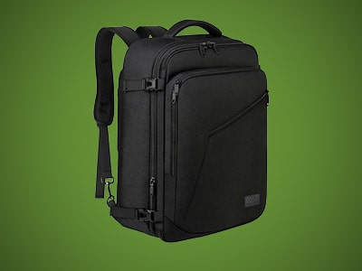 a black carry-on backpack on a green background