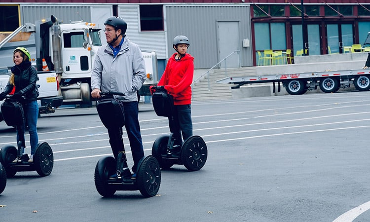 A family riding three segways with helmets on a street