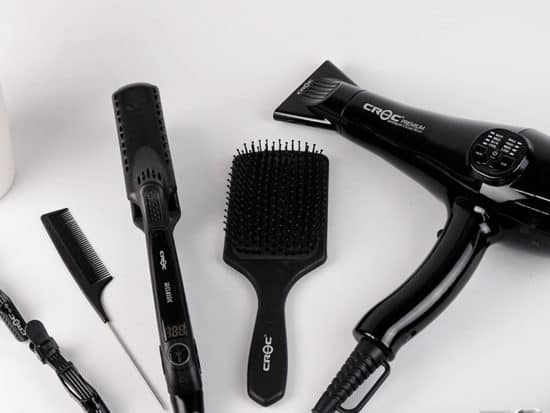 a hairdryer, a hair straightener, a comb, and a rats tail comb on a white background