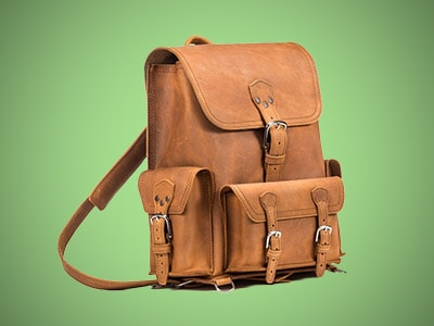 a brown leather backpack on a green background