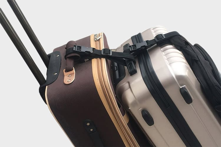 luggage hooked together with luggage straps on a gray background