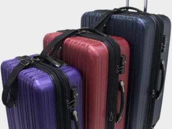 Luggage set hooked together on a gray background