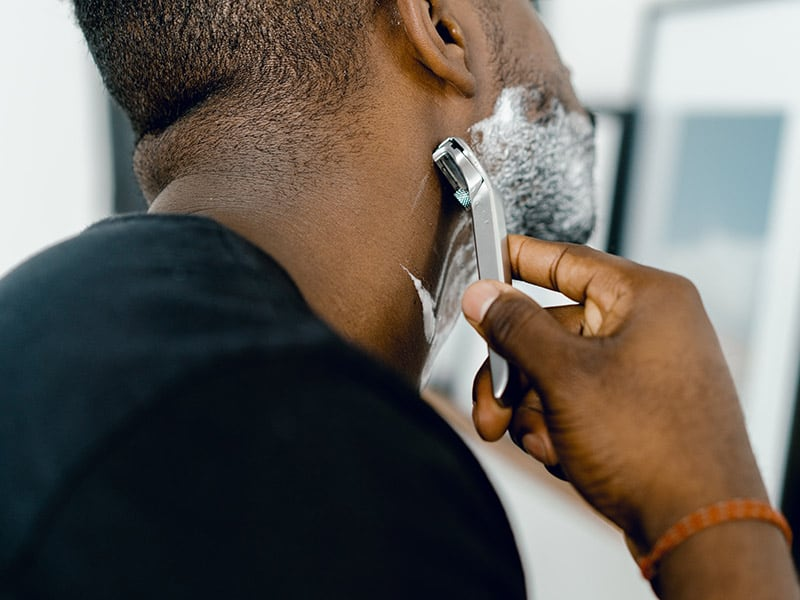 a man shaving using a double edge safety razor and shaving foam