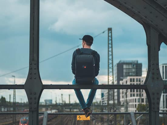 a man sitting on a metal ledge with a black laptop backpack