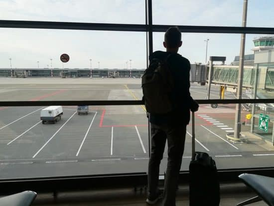 man standing in airport with luggage