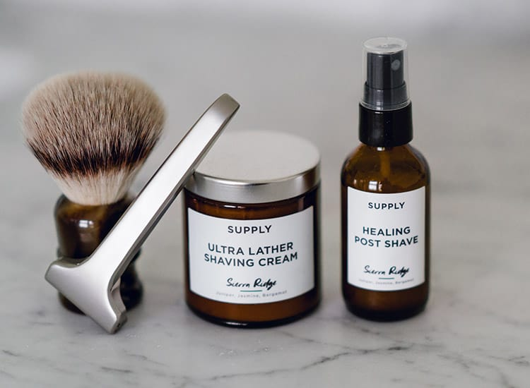 various shaving accessories: shaving cream, brush, aftershave, and a razor on a marble white background