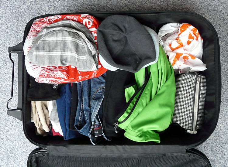 Unpacking an opened suitcase with clothes